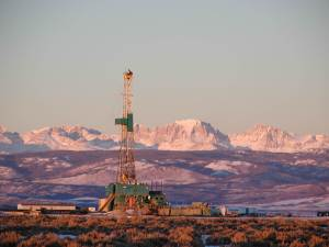 Hydraulic fracturing drilling rig on the Pinedale Anticline in Wyoming with mountain range in background.