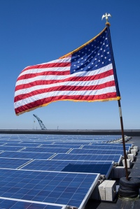 Photo by Ben Bocko of solar panels and an American flag on top of the governor's office in Boston, Massachusetts.